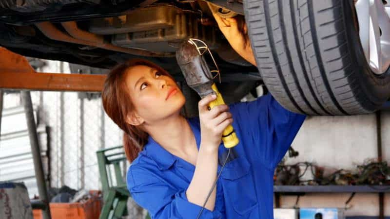 Woman working underneath vehicle using the appropriate equipment